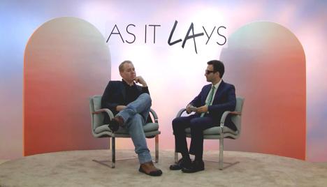 video still of artist interviewing subject on set