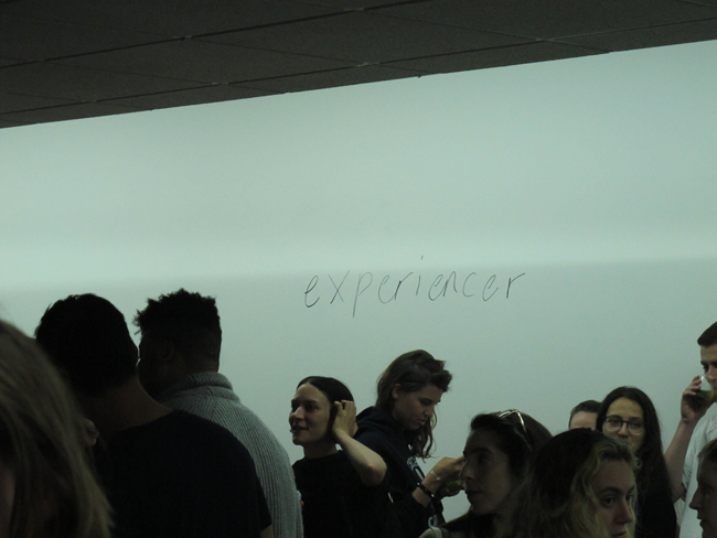 the word experiencer written on the wall seen behind the heads of people