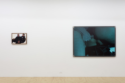 installation view of two photos, one with a cop holding another and the other one with a penis penetrating a butthole