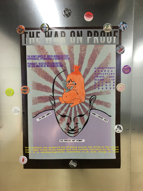 image of poster saying The War on Proof and a little troll on a bald head with magnets on a metallic wall