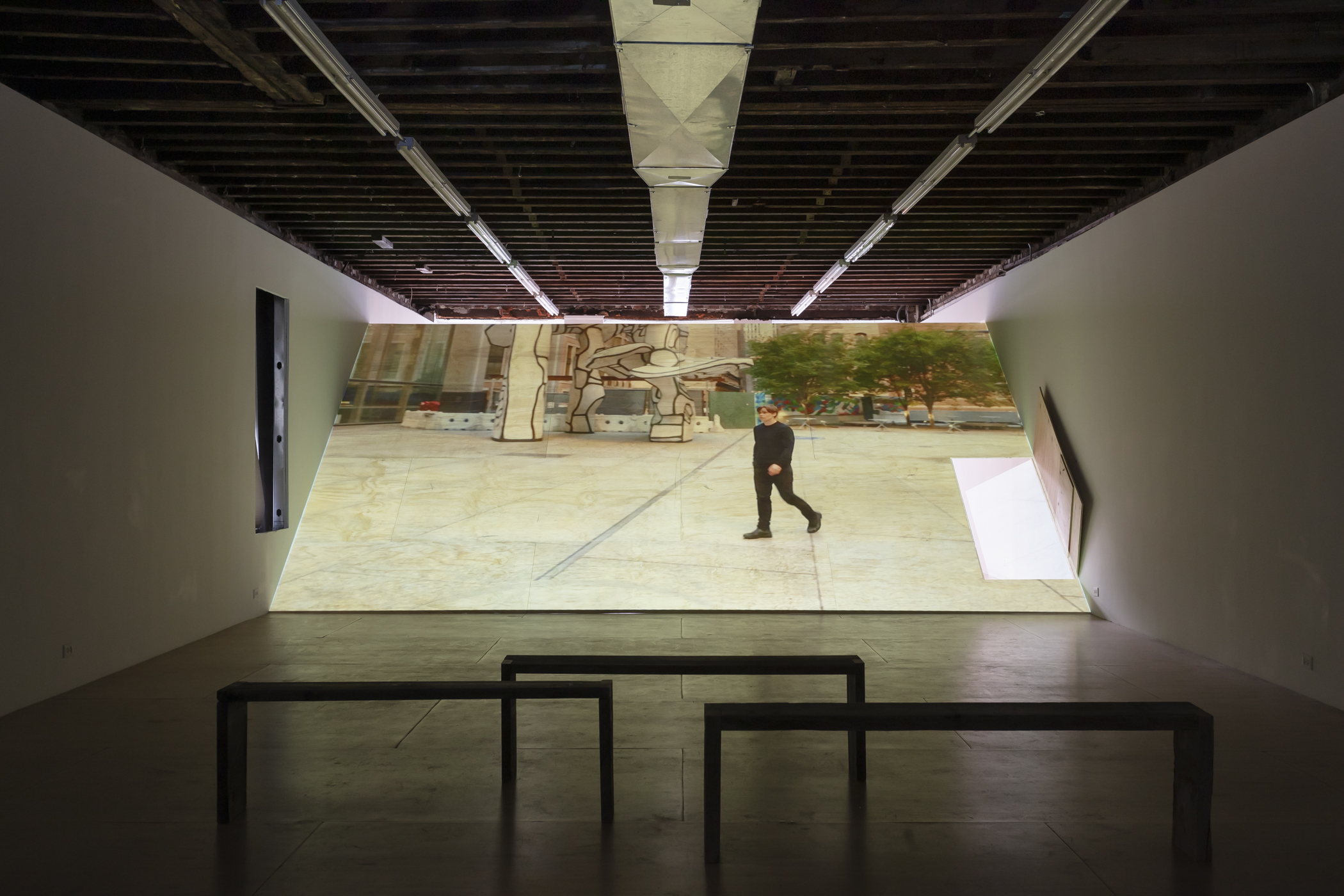 video still of artist falling on pavement projected onto wooden ramp
