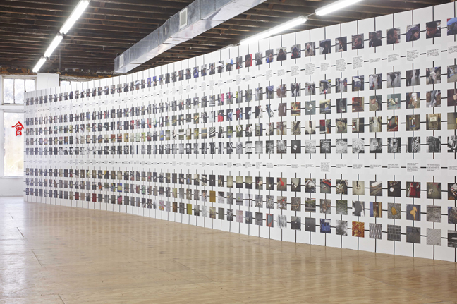 installation image of grids of photographs on a wall