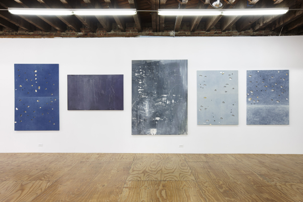 installation image of paintings made of stretched distressed denim