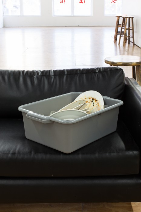 dishwashing bucket with dirty dishes on leather couch